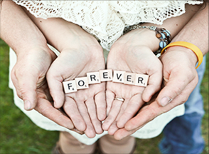 Two pairs of hands, holding wooden tiles spelling 'forever'